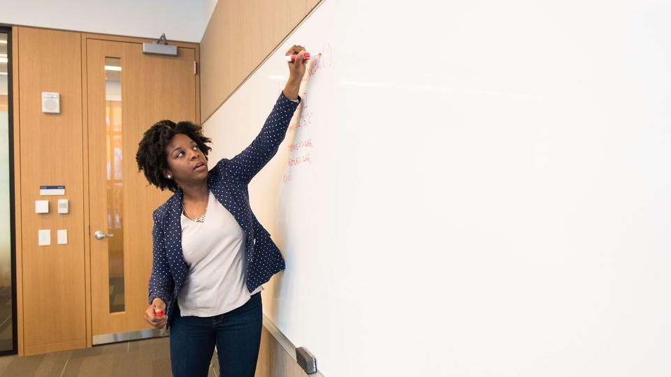 Prefeitura de Santa Helena: a foto mostra uma professora dando aula, fazendo anotações em um quadro branco com pincel vermelho
