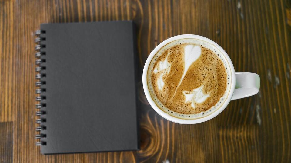 Prefeitura de Santa Rosa do Purus: caderno de capa preta fechado ao lado de xícara de café