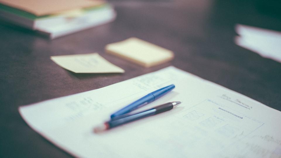 Processo seletivo Prefeitura de Santa Teresa - ES: papéis sob mesa; em cima dos papéis estão duas canetas