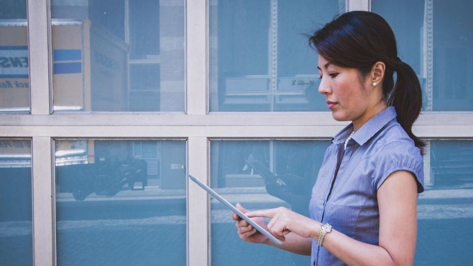 Processo seletivo Prefeitura de Santa Terezinha - SC: edital no ar - a foto mostra uma mulher asiática usando um celular