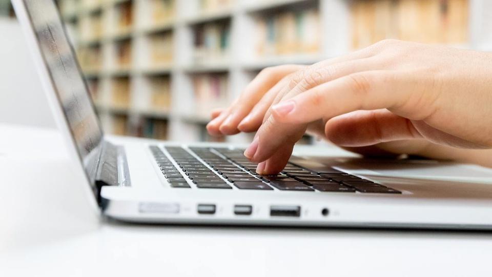 Processo seletivo Prefeitura de Santo Antônio do Monte - MG: foco em mãos digitando em teclado de notebook
