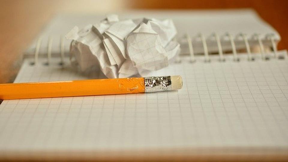 Prefeitura de São João Batista: imagem de um caderno com espiral. Em cima dele há um lápis-borracha amarelo e uma folha amassada.
