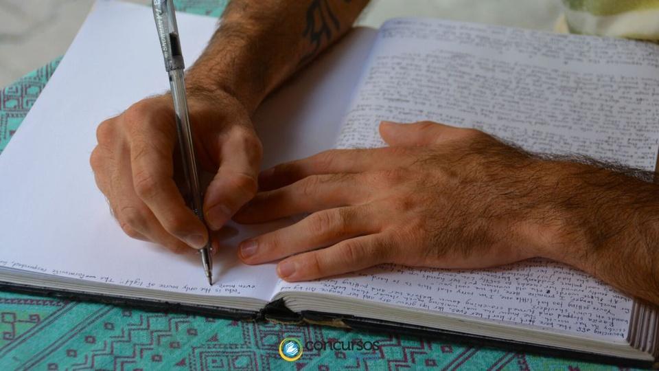 Prefeitura de São José da Boa Vista PR: a foto mostra as mãos de um homem debruçadas sobre um caderno; ele faz anotações de caneta com a mão direita