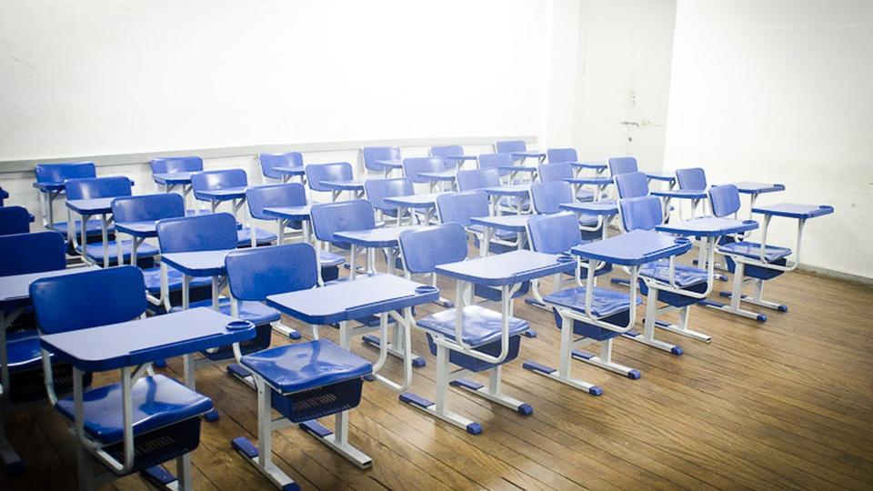 Processo seletivo Prefeitura de São Sebastião do Paraíso - MG: sala de aula vazia com carteiras