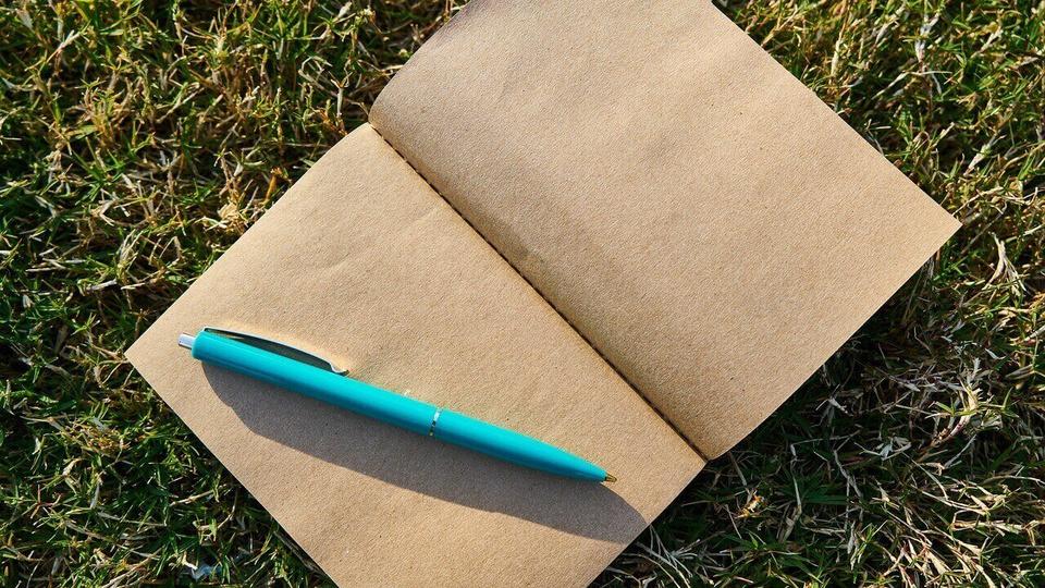 Processo Seletivo Prefeitura de Sapopema - PR: a foto mostra caderno aberto sobre a grama com caneta em cima