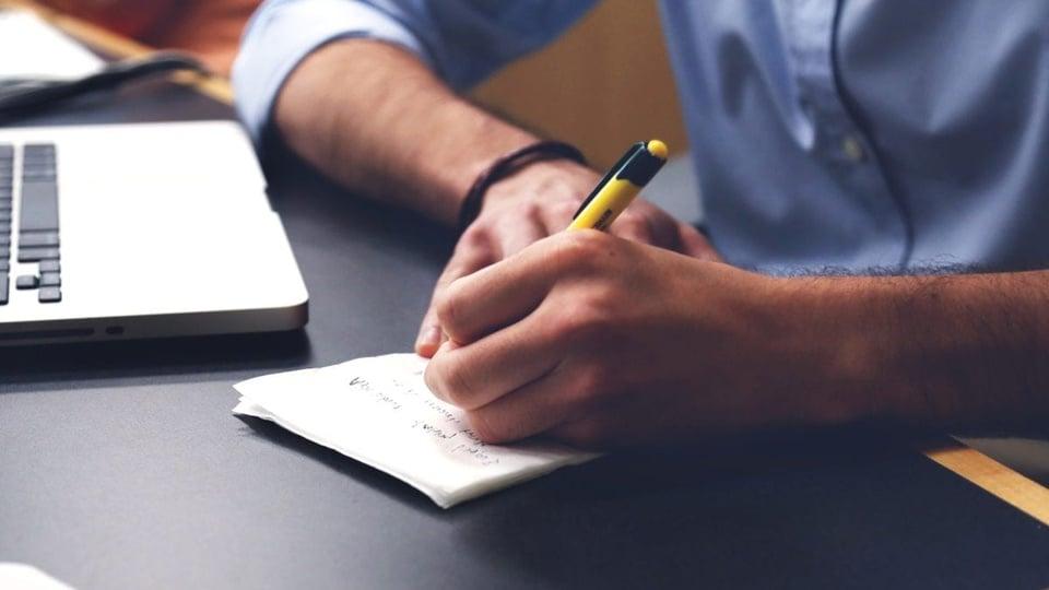 Processo seletivo Prefeitura de Saudades - SC: homem escreve em folha de papel