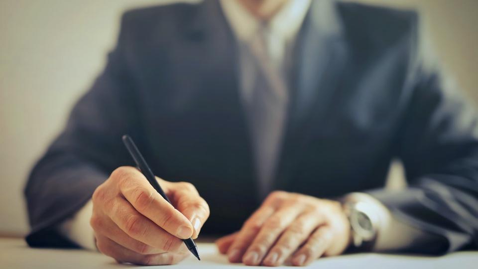 Processo seletivo Prefeitura de Xavantina: homem de terno escrevendo em papel