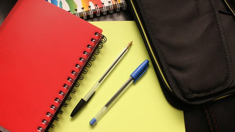 Prefeitura de Dom Feliciano: cadernos nas cores amarela e vermelha sobre mesa, juntamente com duas canetas