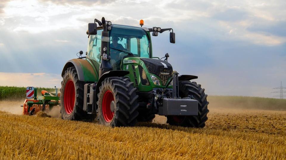 Processo seletivo Prefeitura de Itapoá -  imagem de um trator agrícola verde sendo guiado em um campo