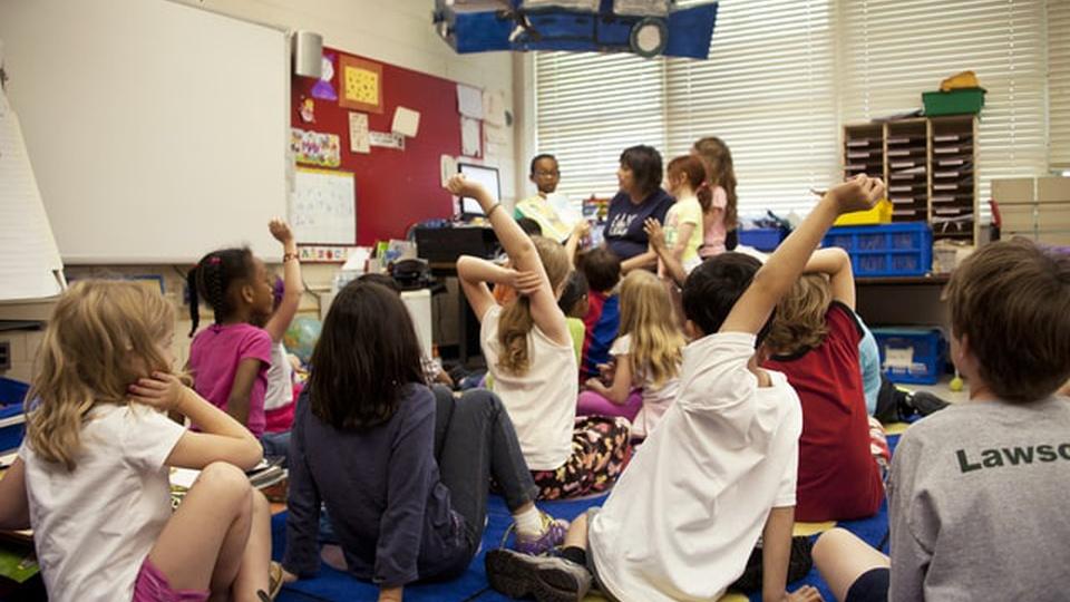 Prefeitura de Paulicéia: crianças em uma sala de aula. Enquanto a professora explica algo, vários alunos estão com as mãos levantadas.