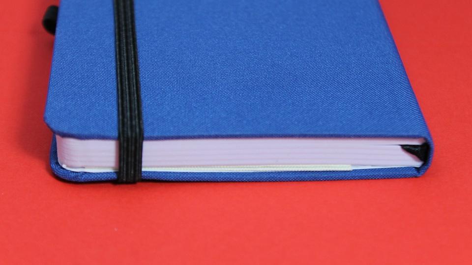 Prefeitura de Tocos do Moji: a imagem mostra caderninho de capa azul fechado em fundo vermelho
