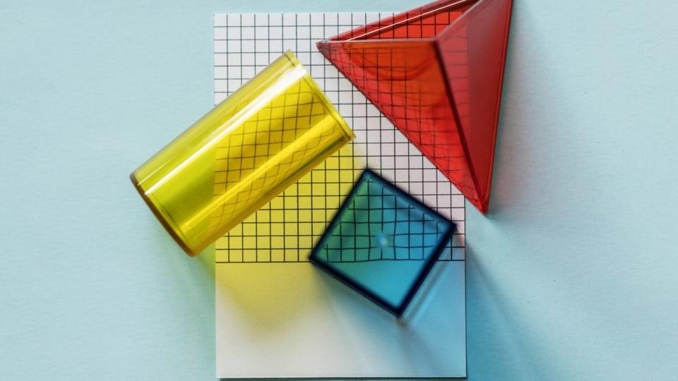 prisma: a imagem mostra prisma triangular e cúbico mais cilindro em cima de papel quadriculado