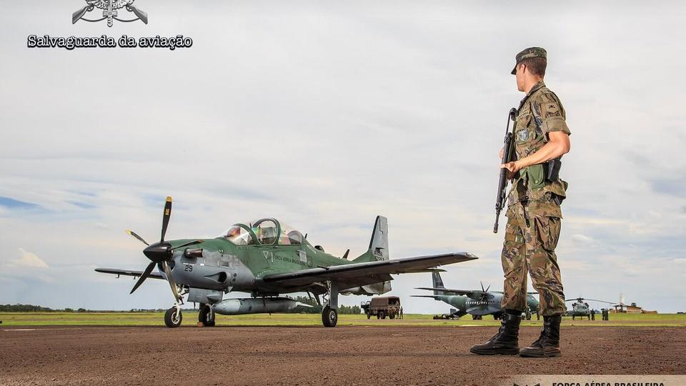 processo seletivo aeronáutica: a imagem mostra soldado em frente a avião da força aérea