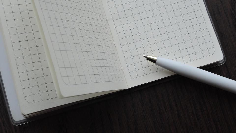 processo seletivo AMVER MG: a imagem mostra caneta de material branco apoiada em caderno aberto