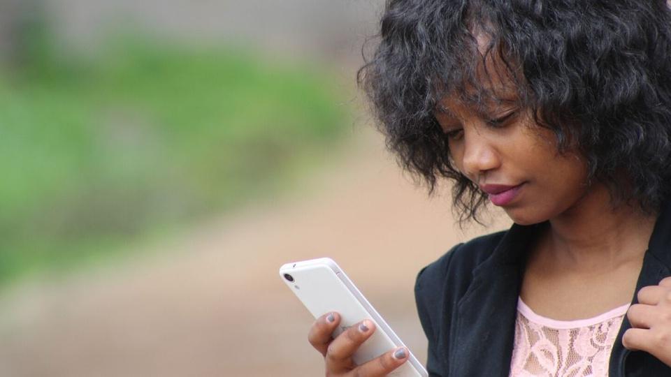 Processo seletivo Câmara de Catas Altas - MG: extrato de edital no ar. A foto mostra uma mulher negra mexendo no celular