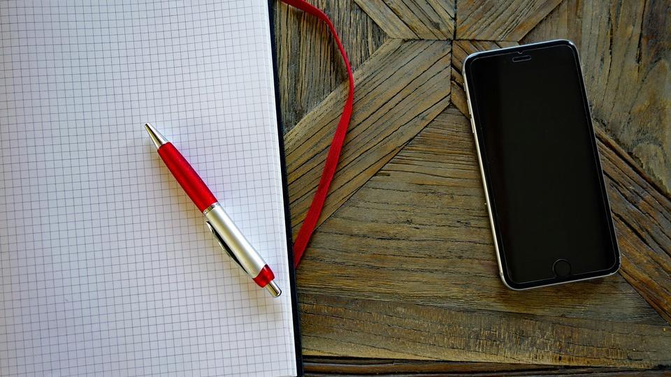 Processo seletivo Câmara de Imbuia - SC: a imagem mostra caderno com folha milimetrada, caneta em cima e, ao lado, um aparelho celular com a tela desligada