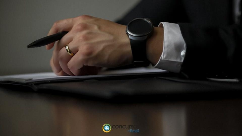 processo seletivo da prefeitura de apodi rn: foco em braço masculino, relógio no pulso e caneta nas mãos, sob folha de papel