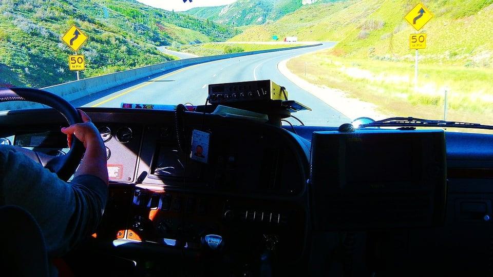 Processo seletivo DEMLURB - MG: motorista dirigindo veículo; foco na estrada vazia.