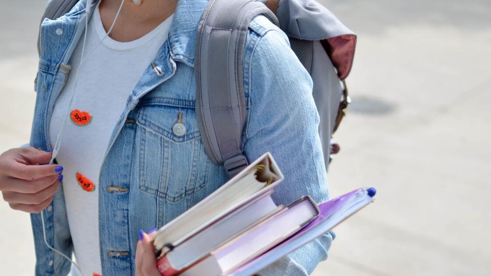 Processo seletivo DPE MA (Defensoria): é possível ver, do pescoço para baixo, uma jovem segurando livros e com uma mochila nas costas