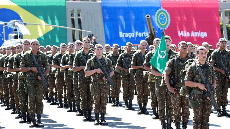 Processo seletivo Exército Brasileiro 11ª Região Militar: exército em formação segurando armas em frente bandeira do brasil e bandeira do exército