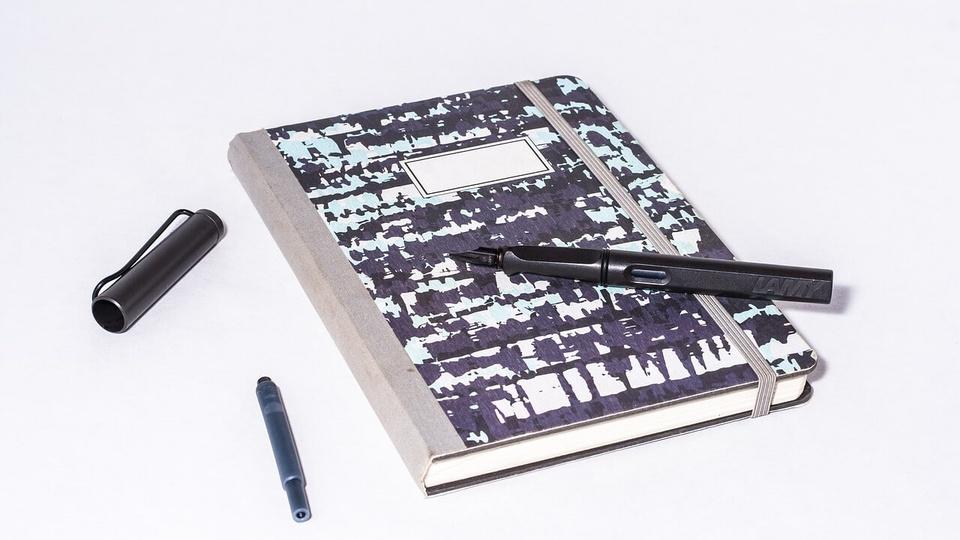 processo seletivo FAHECE: caderno preto e branco fechado com caneta marcadora em cima e a tampa da caneta ao lado