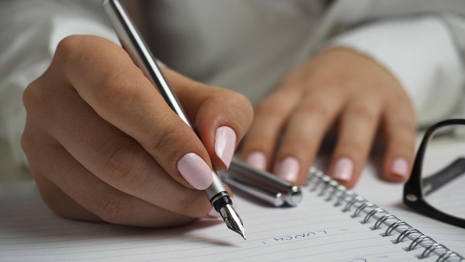 Processo seletivo FAMAP de Porto Belo - SC: foco em mão escrevendo em folha de papel