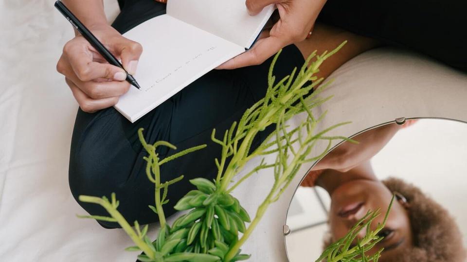 processo seletivo fapespa: a imagem mostra pessoa escrevendo algo em caderno apoiado no joelho