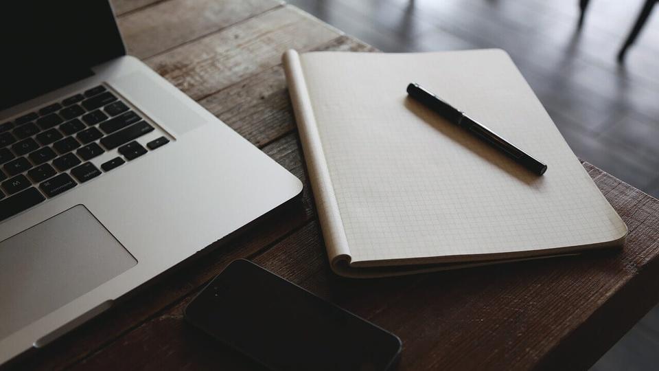 processo seletivo fas curitiba: a imagem mostra notebook ao lado de caderno com caneta em cima