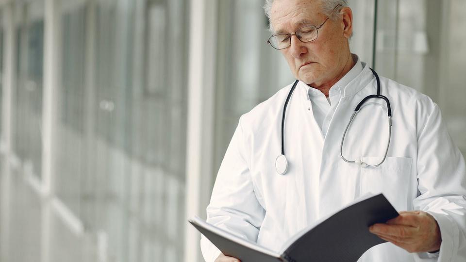 processo seletivo FMSC: médico usando jaleco branco com estetoscópio em volta do pescoço olhando uma apostila aberta