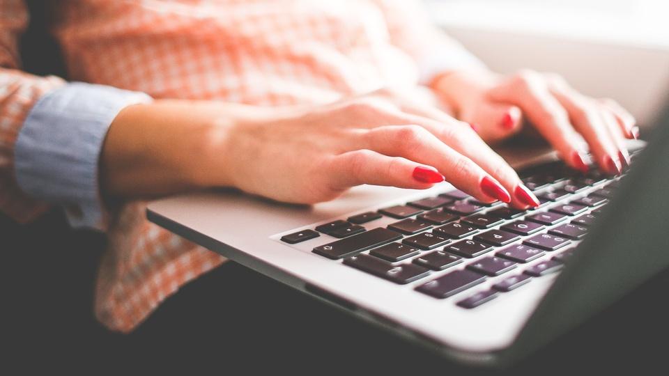 Processo seletivo FSCMP PA: #PraCegoVer mulher de mãos brancas, unhas pintadas de vermelho, sentada em sofá, digitando em teclado de notebook