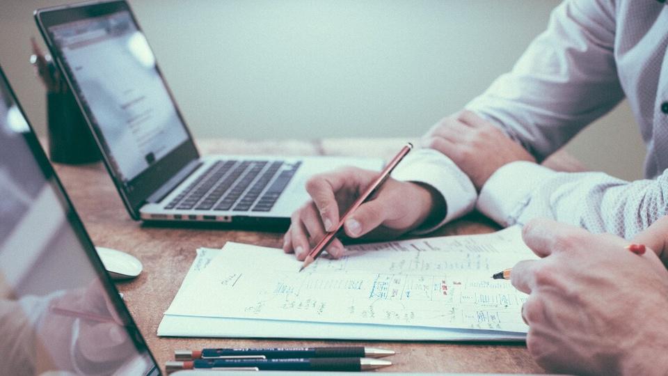 Processo seletivo Fundação Adib Jatene - SP: pessoas escrevendo em papéis com dois notebook em cima da mesa