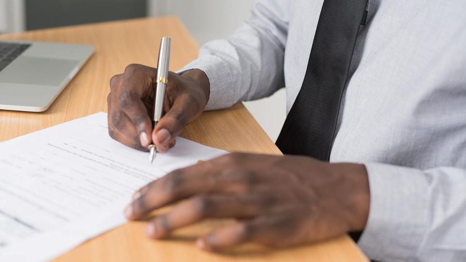 Processo seletivo Fundam: homem escrevendo em folha de papel