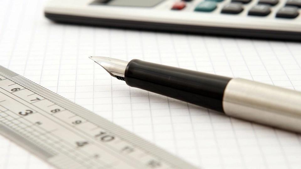 processo seletivo goinfra: a imagem mostra régua, caneta e calculadora sobre folha quadriculada