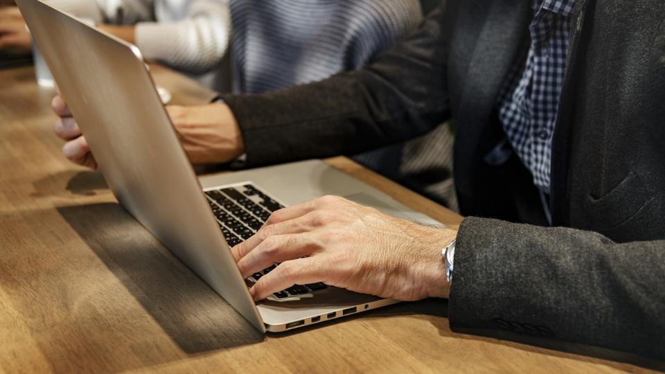 Processo seletivo IAT - PR: homem de terno digitando em teclado de notebook