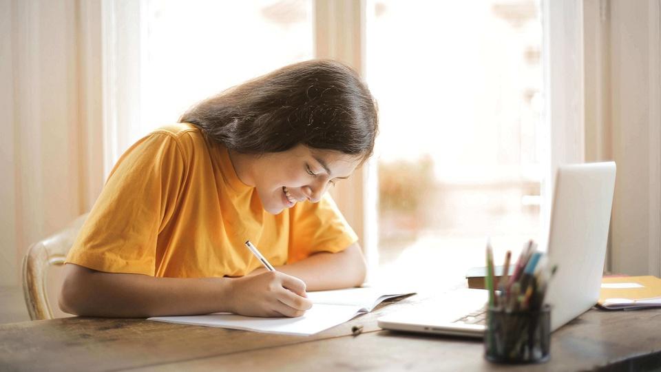 processo seletivo IBRACEDS: a imagem mostra pessoa vestindo camiseta amarela escrevendo algo em papel. Sobre a mesa há um notebook aberto e um potinho com vários lápis e canetas.