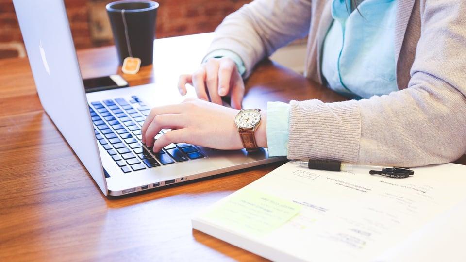 Processo seletivo IDTECH - GO 2021 - #PraCegoVer mulher utilizando notebook, ela tem um relógio de ponteiro no pulso esquerdo, é branca, há uma xícara preta com um sachê de chá à mostra e um livro aber