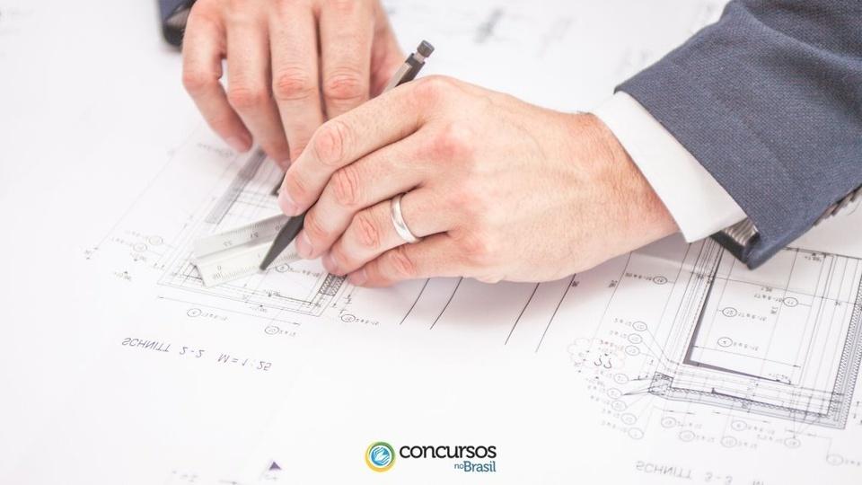 Processo seletivo IEMA: a foto mostra um profissional fazendo cálculos e medições sobre um papel contendo impressa uma planta de engenharia ou arquitetura