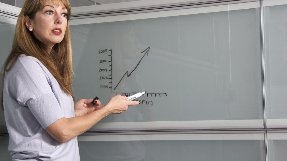 Processo seletivo IFG: professora com pincel na mão em frente a quadro branco
