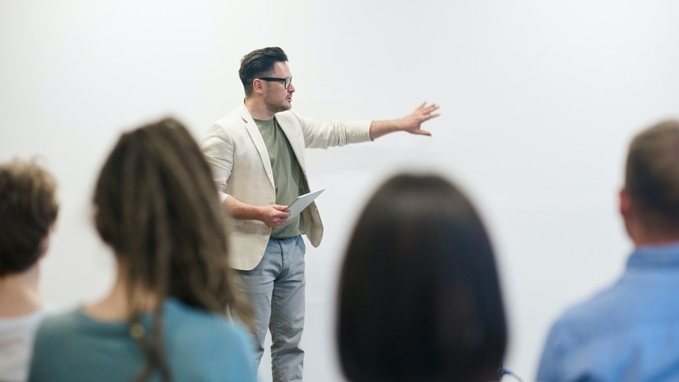 processo seletivo IFTO: foto de sala de aula com alunos desfocados e professor à frente explicando algo no quadro branco