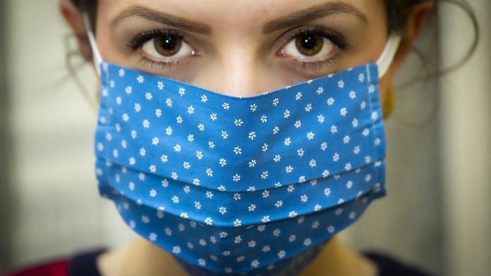 Processo seletivo Itapetim - PE: mulher usando máscara de tecido azul com bolinhas brancas e de olhos bem abertos, indicando alerta