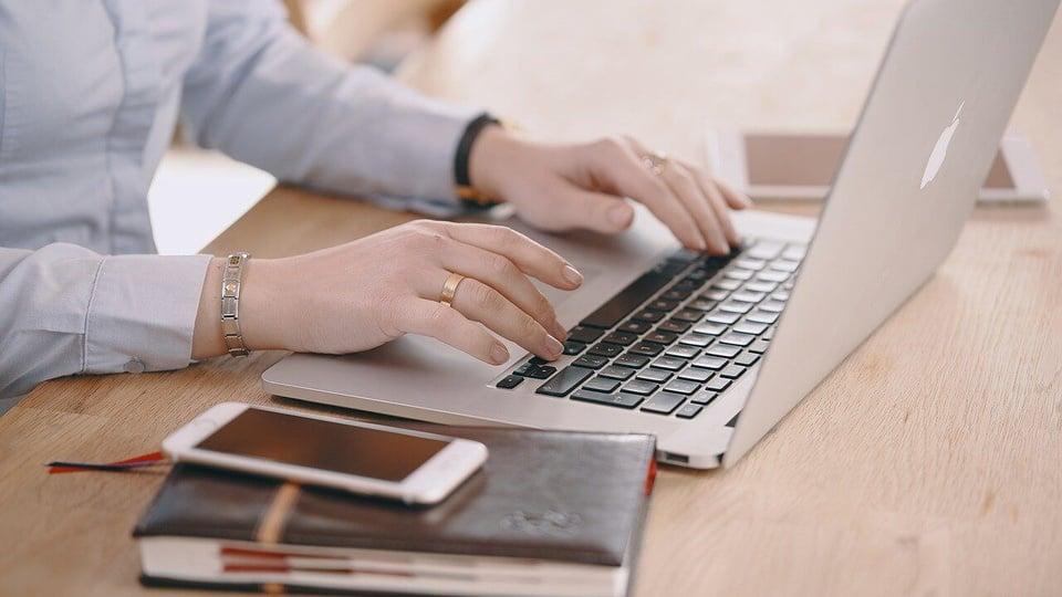 Processo seletivo ITERPA: mãos digitando no notebook. Ao lado, um caderno com celular em cima.