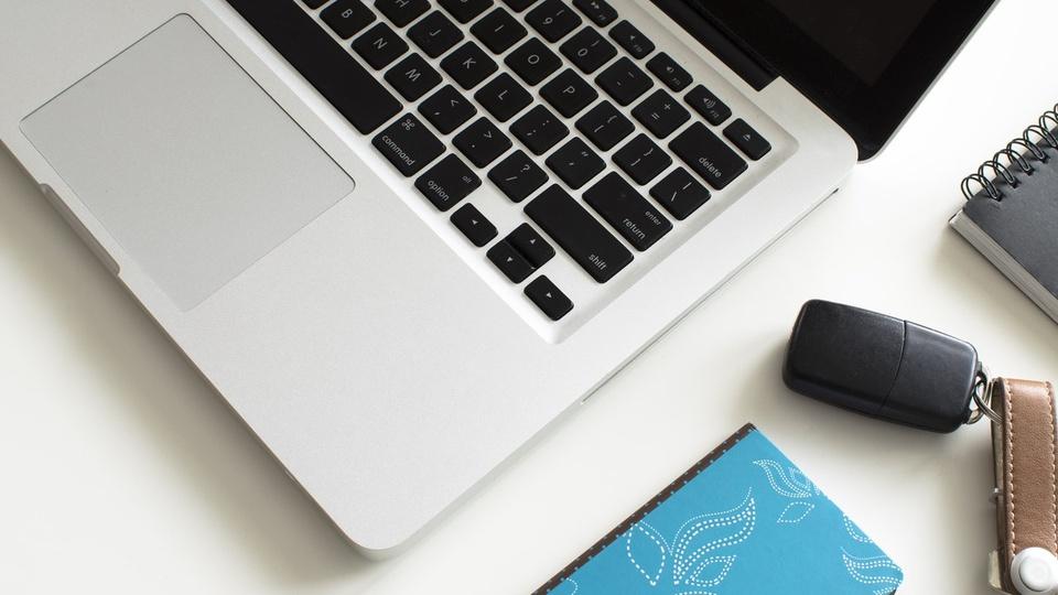 processo seletivo pge am: a imagem mostra um notebook aberto ao lado de bloco de anotação azul e chave de carro