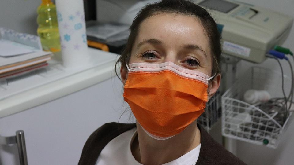 Processo seletivo Policlínica Ribeira do Pombal - BA: mulher jovem, em um consultório clínico, de máscara