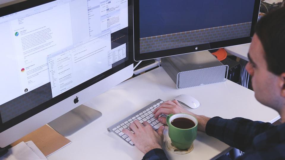 Processo seletivo Prefeitura de Anamã - AM 2021: a foto mostra um homem branco digitando em um computador, em sua frente há dois monitores ligados e entre as mãos que digitam há uma xícara verde cheia de café