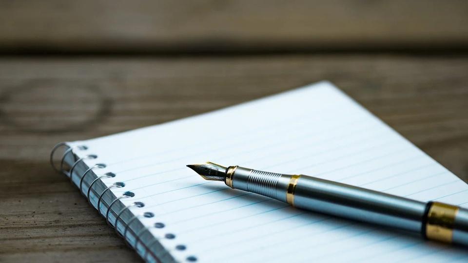 Processo seletivo Prefeitura de Atalanta: a imagem mostra uma caneta tinteiro, bico de pena, de luxo, metálica, sobre caderno aberto