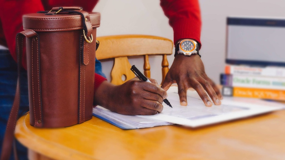 Processo seletivo Prefeitura de Aurora - SC: enquadramento em mão escrevendo em papel disposto em mesa. A pessoa aparenta estar em pé enquanto escreve. É possível ver uma bolsa em cima da mesa