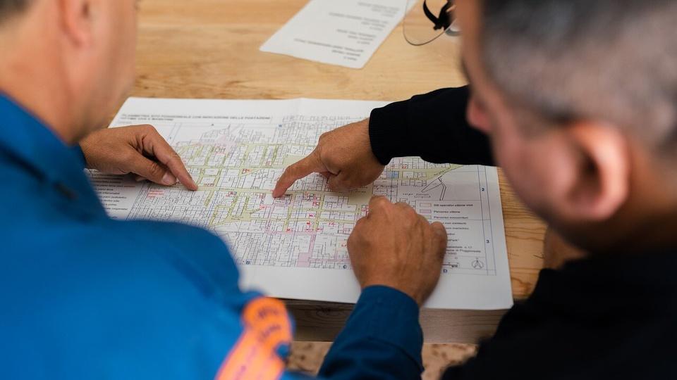 Prefeitura de Bom Despacho: a foto mostra provavelmente engenheiros ou arquitetos trabalhando e lendo uma planta de imóvel