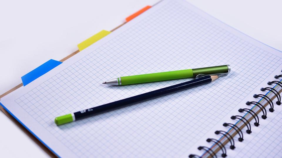 Processo seletivo Prefeitura de Brunópolis - SC: #PraCegoVer a imagem mostra lápis e caneta sobre caderno aberto