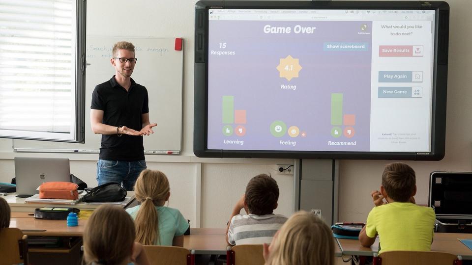 Processo seletivo Prefeitura de Caçapava - SP: profissional da educação, em sala de aula, falando com crianças