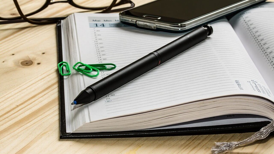 Processo seletivo Prefeitura de Cacaulândia:  a imagem mostra caderno aberto com lápis, clipe e celular em cima. Atrás há um óculos.